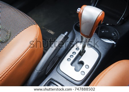 Automatic gear stick with manual selection option.Detail on a automatic gear shifter in a luxury car. #747888502