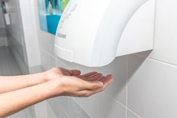 Automatic hand dryer in public toilet or restroom hygiene concept. A man hands using utomatic hand dryer in bathroom.