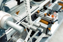 Automatic labeling machine. The labeled tape is located between the feed rollers.