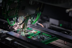 Automatic machine for diagnostics of electronic boards, production. Small needles are checking the electronic circuit. Creation of electronic boards and microcircuits. Processor manufacturing.