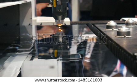 Automatic mechanism of laser cutting for metal on the exhibition area, close-up. Media. Electronic devices and mechanisms are presented at the scientific exhibition.