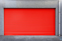 Automatic red metal roller shutter doors on the ground floor of the house