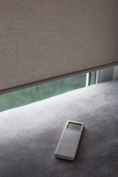 Automatic roller blinds beige color on the window. White remote control panel for motorized roller shades.  Remote Control Shades are near the sofa. Remote control lies on the sofa.