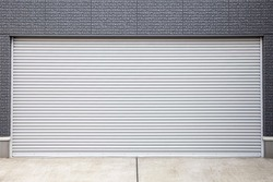 Automatic silver metal roller shutter doors on the ground floor of the house