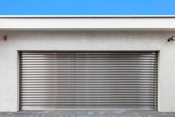 Automatic silver roller shutter doors on the ground floor of the house