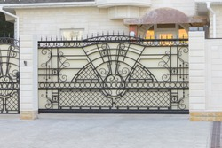 Automatic sliding gates with wrought ornaments of white color in a private house