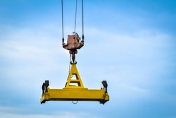 Automatic spreader of an industrial crane hanging in the air with blue sky background