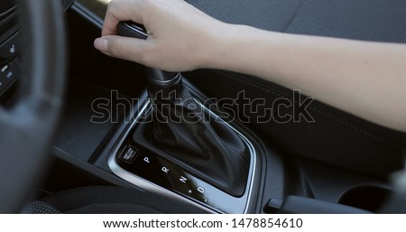 Automatic transmission, automatic gear shift, is moved from D (Drive) to P (Park). Female hand shifts gears.