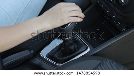 Automatic transmission, automatic gear shift, is moved from P (Park) to D (Drive). Female hand shifts gears.