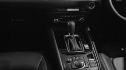 Automatic transmission gear handle and buttons for asia region car with black sport leather seat interior.