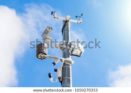 Automatic weather station, with a weather monitoring system and video cameras for observation. Against the background of a blue sky with clouds. #1050270353