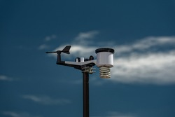 Automatic weather station, with weather monitoring system and weather observation. Against the background of a blue sky with clouds. Selective focus.