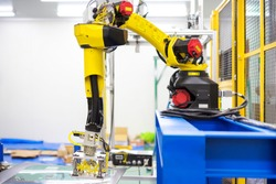 Automation concept: View of inspection unit on industrial robot arm in automative windshield manufacture plant