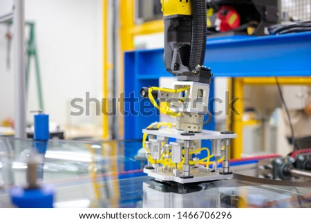 Automation concept: View of inspection unit with camera on robot arm of glass sealing process  in automation line