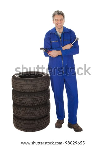 Automechanic standing next to car tires. Isolated on white