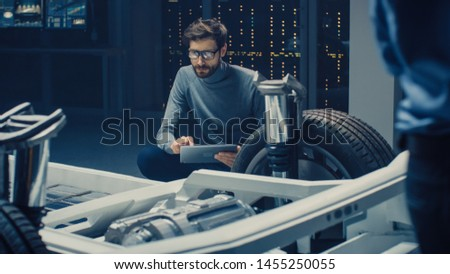 Automobile Design Engineer Sitting Beside Hybrid Electric Car Chassis Platform Prototype, Using Tablet Computer for Design Enhancement. Facility with Vehicle Frame with Suspension, Engine and Battery