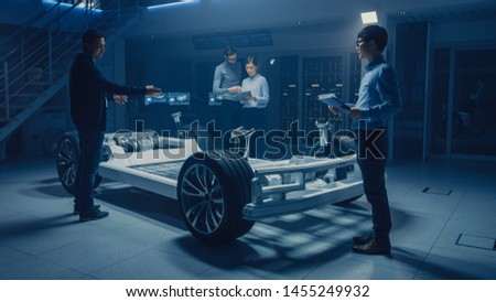 Automobile Design Engineers Working on Electric Car Platform Chassis Prototype, Using CAD Software for 3D Concept. In Automotive Innovation Facility Vehicle Frame with Tires, Suspension, Engine