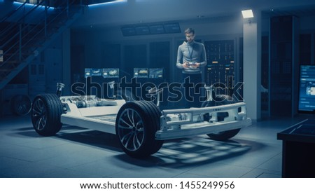 Automobile Engineer Work on Electric Car Platform Chassis Prototype, Using Tablet Computer with 3D CAD Software Modelling. Innovative Facility: Vehicle Frame with Wheels, Engine,Battery and Suspension