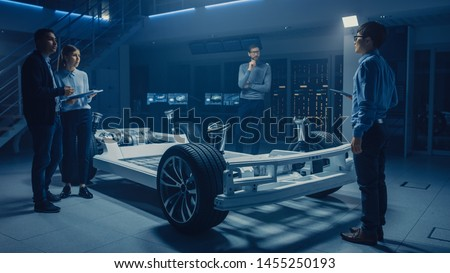 Automobile Engineers Designing Electric Car Platform Chassis Prototype, Using Tablet Computers with CAD Software for 3D Concept. In Automotive Innovation Facility Vehicle Frame with Wheels, Engine
