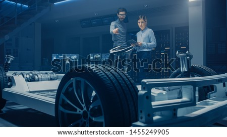 Automobile Mae and Female Design Engineers Working on Electric Car Platform Chassis Prototype, Using CAD Software for 3D Concept. In Automotive Innovation Facility Vehicle Frame with Tires, Suspension