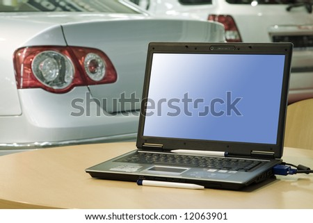 automobile sales center (laptop with empty screen for your design or ads)