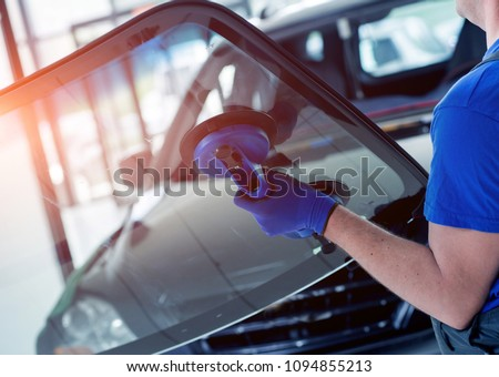 Automobile special workers replacing windscreen or windshield of a car in auto service station garage. Background #1094855213