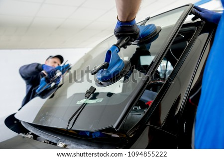Automobile special workers replacing windscreen or windshield of a car in auto service station garage. Background #1094855222
