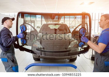 Automobile special workers replacing windscreen or windshield of a car in auto service station garage. Background - Shutterstock ID 1094855225