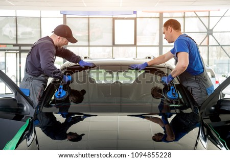 Automobile special workers replacing windscreen or windshield of a car in auto service station garage. Background - Shutterstock ID 1094855228