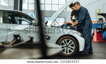 Automobile technicians using electronic diagnostic equipment to tune a car. Mechanics using a device to check the engine.
