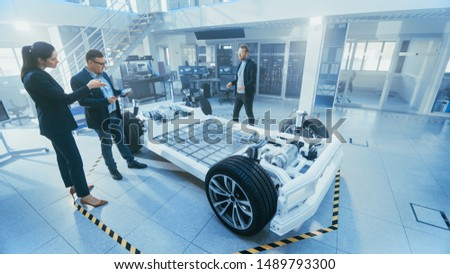 Automotive Design Engineer Shows the Electric Car Chassis Prototype to the Management Board Representatives. Concept Includes Wheels, Hybrid Engine and Battery.