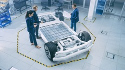 Automotive Design Engineers Talking while Working on Electric Car Chassis Prototype. In Innovation Laboratory Facility Concept Vehicle Frame Includes Wheels, Suspension, Engine and Battery.