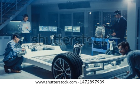 Automotive Design Engineers Work and Do Tests on Electric Car Chassis Prototype. In Innovation Laboratory Facility Concept Vehicle Frame Includes Wheels, Suspension, Engine and Battery.