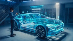 Automotive Engineer Uses Digital Tablet with Augmented Reality for Car Design Analysis and Improvement. 3D Graphics Visualization Shows Fully Developed Vehicle Prototype Analysed and Optimized