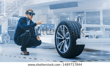 Automotive Engineer Working on Electric Car Chassis Platform, Using Augmented Reality Headset. In Innovation Laboratory Facility Concept Vehicle Frame Includes Wheels, Suspension, Engine and Battery.