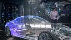 Automotive Female Professional Engineer working on design of Electric Car using Futuristic Augmented Reality Headset with Holographic Technology. High-tech facility. Electric car chassis.