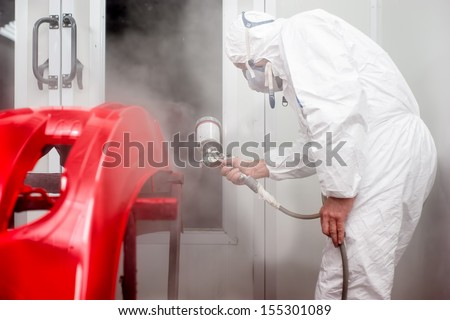 Automotive industry - worker painting and working on the body of a car