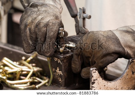 AUTOMOTIVE INDUSTRY WORKER WEARING USED PROTECTION GLOVES