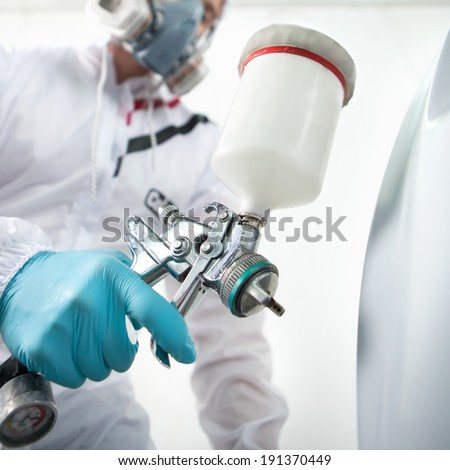Automotive Paint Mechanic Painting the Car in Auto Repair Shop