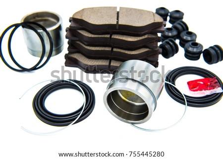 Automotive Spare Parts of disk brake pads, disc brake caliper piston, disk brake repair kIt and rotating brake disk on white background. #755445280