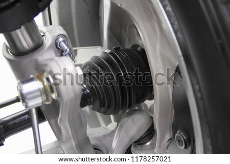 Automotive transmission parts - close up driveshaft, tripod CV-joint, shock adsorber, stabilizer, levers, disk and tire of new concept car in profile #1178257021