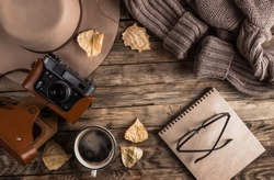 Autumn accessories flat lay. Hat, brown sweater, notebook, cup of coffee, eyeglasses, retro camera