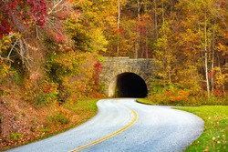 Autumn along The Blue Ridge Parkway in North Carolina with stone tunnel on curvy road