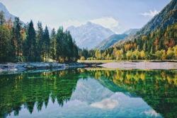 Autumn alps mountains in day light reflected in calm waters of green lake Jasna, Kranjska Gora. Slovenia.