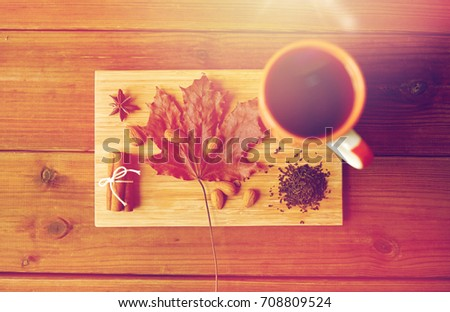 autumn and season concept - cup of tea, maple leaf and almond on wooden board #708809524