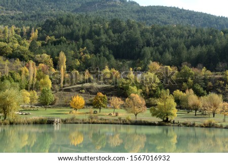 Autumn around a lake in South France, Trees with autumnal colors. A pontoon, picnic tables, fishers.