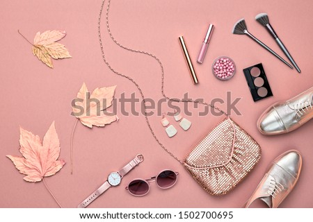 Autumn Arrives. Fall fashion Accessories cosmetics set. Creative Flat lay. Trendy Stylish gold loafers shoes, glamour handbag, makeup product, fashionable party look. Autumnal color, shopping concept
