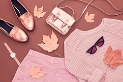 Autumn Arrives. Fashion Lady Clothes Set. Trendy Cozy Jumper. Stylish Gold Handbag Clutch, Glamour Sunglasses. Flat lay. Fall Leaves. Vanilla Pastel autumnal fashionable colors.
