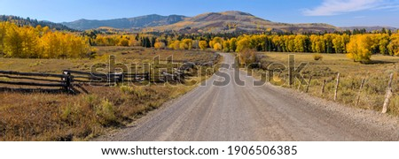 Autumn at Owl Creek Pass Road - A panorama of Owl Creek Pass Road running through rolling ranch land toward colorful mountain forest on a sunny Autumn afternoon. Ridgway, Colorado, USA.