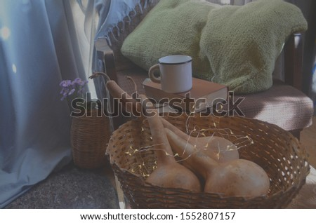 Autumn atmosphere. Hobby concept. Cozy rustic interior with metal mug book and pumpkins selective focus. #1552807157
